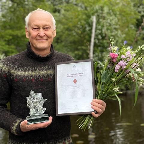 Man står i naturen och håller i blommor, diplom och glas statyett. Foto
