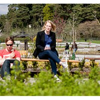 Two students drink coffee in the Knowledge Garden. Photo.