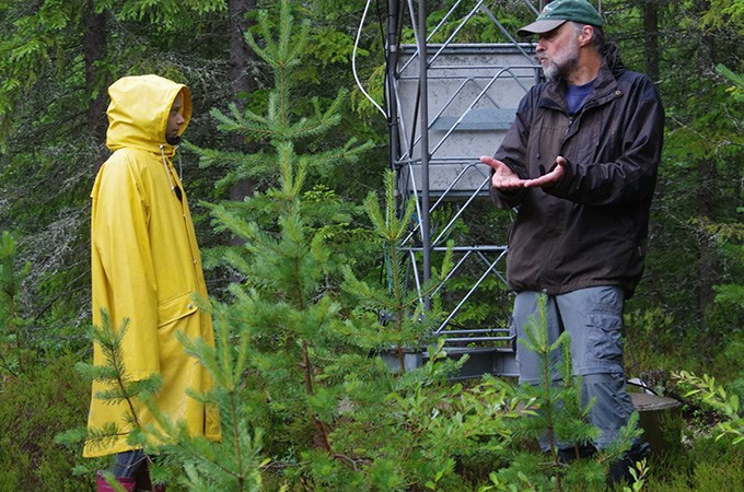 Woman in yellow raincoat and a man in a dark jacket are having a discussion in the forest.