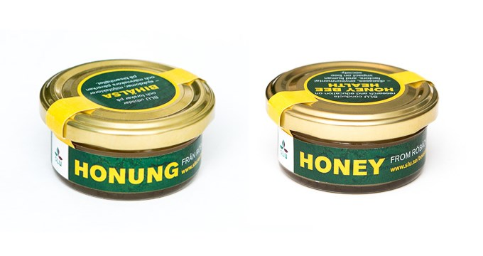 Picture of two small jars of honey made at SLU in Röbäcksdalen. The labels of the jar shas yellow text on a dark green background and the left one is written in Swedish and the right one is in English.