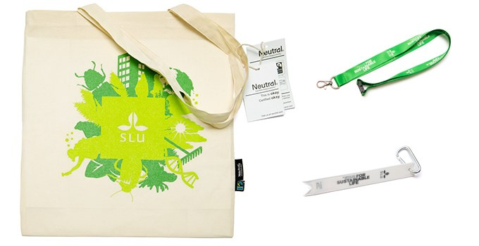 Picture of the SLU tote bag in off white with a green SLU brand print, a green key strap with a SLU logo and a white clip-on reflector with a black SLU logo and brand promise.